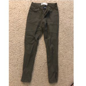 Olive green jeans with zippers at the ankles